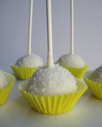 Lemon Cake Pops Lemon cake with cream cheese frosting covered in white chocolate, and topped with sugar crystals.